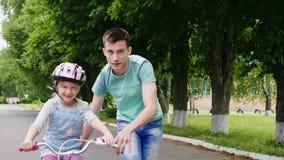 Ο μεγάλος αδερφός διδάσκει την αδελφή του πώς να οδηγήσει ένα ποδήλατο, οι πρώτες επιτυχίες των παιδιών απόθεμα βίντεο
