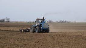 Ο μεθύστακας και χαλαρώνει το χώμα στον τομέα πρίν σπέρνει Το τρακτέρ οργώνει έναν τομέα με ένα άροτρο φιλμ μικρού μήκους