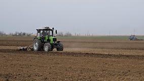 Ο μεθύστακας και χαλαρώνει το χώμα στον τομέα πρίν σπέρνει Το τρακτέρ οργώνει έναν τομέα με ένα άροτρο απόθεμα βίντεο