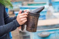 Ο μελισσοκόμος κρατά μια καπνοδόχο στο χέρι του για τον υποκαπνισμό των μελισσών στοκ φωτογραφία με δικαίωμα ελεύθερης χρήσης