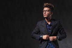 Ο μεμβρανοειδής νεαρός άνδρας που φορά τα γυαλιά καθορίζει το σακάκι του στο στούντιο Στοκ φωτογραφίες με δικαίωμα ελεύθερης χρήσης