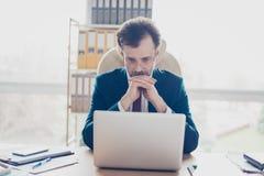 Ο μεσίτης επιχειρηματιών στρέφεται και εξετάζοντας το lap-top του Είναι W στοκ φωτογραφίες