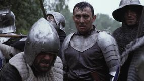 Ο μεσαιωνικός ιππότης στο τεθωρακισμένο πιάτων στέκεται στη μέση του πεδίου μάχης φιλμ μικρού μήκους