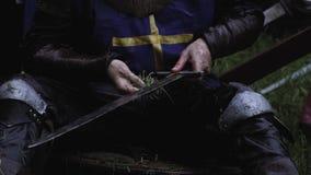Ο μεσαιωνικός στρατιώτης καθαρίζει το ξίφος του κάτω από τη βροχή με τη χλόη, κλείνει επάνω φιλμ μικρού μήκους
