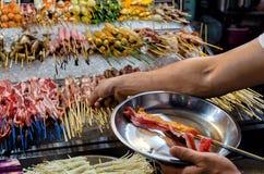 Ο μετρητής με τα κινεζικά τρόφιμα οδών, ο αγοραστής γεμίζει ένα πιάτο με το μπέϊκον τρόφιμα στα ραβδιά στοκ φωτογραφία με δικαίωμα ελεύθερης χρήσης