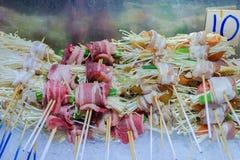 Ο μετρητής τροφίμων οδών, μανιτάρια ψήνει στη σχάρα, ρόλος μανιταριών με το μπέϊκον, δέσμες enoki με το κρέας στοκ εικόνα