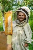 Ο μελισσοκόμος αγοριών κρατά στα χέρια του μια κηρήθρα με το φρέσκο μέλι Μελισσοκομία φρέσκο μέλι Στοκ Φωτογραφία