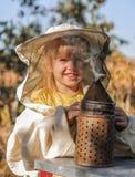 Ο μελισσοκόμος μικρών κοριτσιών φυσά τον καπνιστή για τις μέλισσες Στοκ Φωτογραφία