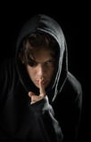 Ο με κουκούλα έφηβος έχει ένα μυστικό στο μαύρο υπόβαθρο Στοκ εικόνα με δικαίωμα ελεύθερης χρήσης