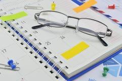 Ο μηνιαίος αρμόδιος για το σχεδιασμό με τα γυαλιά και το τοποθετεί στη γραφική παράσταση εγγράφου Στοκ Εικόνες