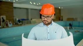 Ο μηχανικός ή ο αρχιτέκτονας κατασκευής στο πορτοκαλί κράνος με μια κατασκευή προγραμματίζει στο υπόβαθρο της κατασκευής απόθεμα βίντεο