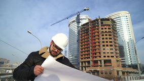 Ο μηχανικός ή ο οικοδόμος ελέγχει και ελέγχει το αντικείμενο κάτω από την κατασκευή Πηγαίνει από το εργοτάξιο οικοδομής, απόθεμα βίντεο