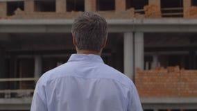 Ο μηχανικός ή ο οικοδόμος ελέγχει και ελέγχει το αντικείμενο κάτω από την κατασκευή Πηγαίνει από το εργοτάξιο οικοδομής, φιλμ μικρού μήκους