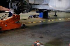 ο μηχανικός αντικαθιστά τον απορροφητή κλονισμού & την άνοιξη στο αυτόματο γκαράζ επισκευής στοκ εικόνες