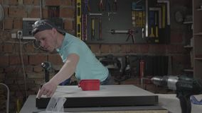 Ο μηχανικός βιοτεχνών πορτρέτου εστίασε στη διάτρυση μιας τρύπας με το εργαλείο στο υπόβαθρο ενός μικρού εργαστηρίου με τα όργανα φιλμ μικρού μήκους