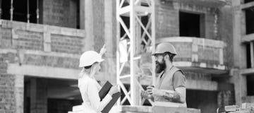Ο μηχανικός γυναικών και ο βάναυσος οικοδόμος επικοινωνούν το υπόβαθρο εργοτάξιων οικοδομής Σχέσεις μεταξύ των πελατών κατασκευής στοκ εικόνες