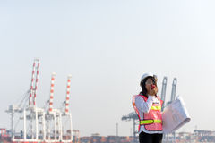 Ο μηχανικός γυναικών που εργάζεται με το σκάφος φορτίου φορτίου εμπορευματοκιβωτίων στο ναυπηγείο στο σούρουπο Στοκ Εικόνες
