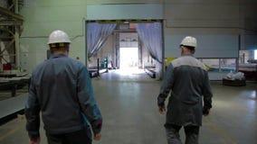 Ο μηχανικός δύο στο σκληρό καπέλο περπατά μέσω του εργοστασίου απόθεμα βίντεο