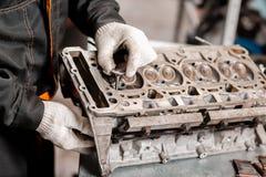 Ο μηχανικός εγκαθιστά μια νέα βαλβίδα Αποσυνθέστε το όχημα φραγμών μηχανών Κύρια επισκευή μηχανών Δέκα έξι βαλβίδες και τέσσερις στοκ εικόνες