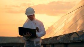 Ο μηχανικός ελέγχει οι ηλιακού πλαισίου, εργαζόμενος με lap-top, κλείνει επάνω φιλμ μικρού μήκους
