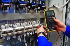 Ο μηχανικός εξετάζει τα βιομηχανικά ηλεκτρικά κυκλώματα με ένα πολύμετρο στο τελικό κιβώτιο ελέγχου Στοκ εικόνες με δικαίωμα ελεύθερης χρήσης