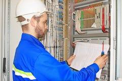 Ο μηχανικός εξετάζει το ηλεκτρικό διάγραμμα σχεδίων στο ηλεκτρικούς γραφείο αυτοματοποίησης και τον έλεγχο του βιομηχανικού εξοπλ Στοκ φωτογραφία με δικαίωμα ελεύθερης χρήσης