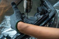 Ο μηχανικός επισκευάζει τον προβολέα, σπασμένο φως αυτοκινήτων στοκ εικόνα με δικαίωμα ελεύθερης χρήσης