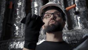 Ο μηχανικός εργάζεται στο δωμάτιο λεβήτων και υπαγορεύει το ακουστικό μήνυμα στο smartphone απόθεμα βίντεο