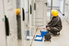 Ο μηχανικός ηλεκτρολόγων εξετάζει το σύστημα με τον καθορισμένο εξοπλισμό δοκιμής ηλεκτρονόμων Στοκ Εικόνα