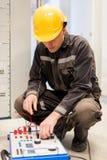 Ο μηχανικός ηλεκτρολόγων εξετάζει το σύστημα με τον καθορισμένο εξοπλισμό δοκιμής ηλεκτρονόμων Στοκ εικόνες με δικαίωμα ελεύθερης χρήσης