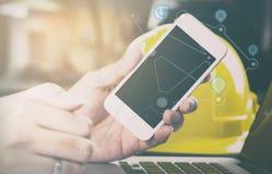 Ο μηχανικός κατασκευής χρησιμοποιεί ένα smartphone για την επικοινωνία Στοκ Φωτογραφίες