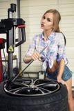 Ο μηχανικός κοριτσιών αντικαθιστά τις ρόδες στις ρόδες στοκ εικόνες με δικαίωμα ελεύθερης χρήσης