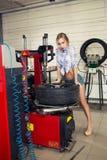 Ο μηχανικός κοριτσιών αντικαθιστά τις ρόδες στις ρόδες στοκ φωτογραφία με δικαίωμα ελεύθερης χρήσης