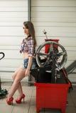 Ο μηχανικός κοριτσιών αντικαθιστά τις ρόδες στις ρόδες στοκ εικόνες