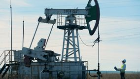Ο μηχανικός με το lap-top ελέγχει το λειτουργώντας πύργο πετρελαίου φιλμ μικρού μήκους