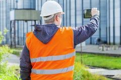 Ο μηχανικός με το PC ταμπλετών κυττάρων στο εργοστάσιο Στοκ Φωτογραφία