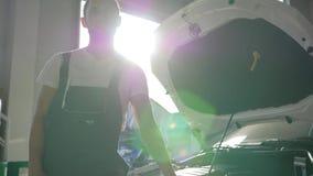 Ο μηχανικός μηχανών πορτρέτου στο backlight ανοίγει πλησίον το καπό, αυτόματη επισκευή εργαζομένων, μηχανικός, κύριος στο πρατήρι απόθεμα βίντεο