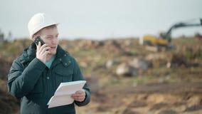 Ο μηχανικός μιλά στο τηλέφωνο, εργαζόμενος έγγραφα και κλήσεις στο υπόβαθρο του εκσκαφέα απόθεμα βίντεο