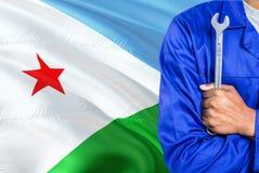 Ο μηχανικός μπλε σε ομοιόμορφο κρατά το γαλλικό κλειδί στο κυματίζοντας κλίμα σημαιών του Τζιμπουτί Διασχισμένος τεχνικός όπλων στοκ εικόνες με δικαίωμα ελεύθερης χρήσης