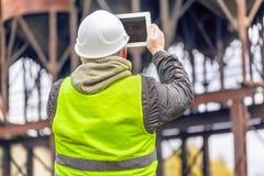 Ο μηχανικός οι δεξαμενές με το PC ταμπλετών στο εργοστάσιο Στοκ εικόνες με δικαίωμα ελεύθερης χρήσης