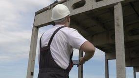 Ο μηχανικός παίρνει τις εικόνες στο έξυπνο τηλέφωνο κοντά στο ατελές κτήριο απόθεμα βίντεο