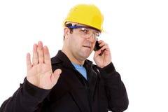 ο μηχανικός που μιλά στο τηλέφωνο και κάνει τη στάση να υπογράψει Στοκ Εικόνα