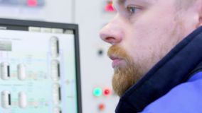 Ο μηχανικός που μιλά walkie-talkie και εξετάζει τους δείκτες οθονών στο θάλαμο ελέγχου φιλμ μικρού μήκους
