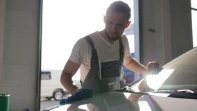 Ο μηχανικός προετοιμάζει τη μηχανή για τον πελάτη, πλύσιμο αυτοκινήτων, backlight, πορτρέτο του ατόμου που τρίβει το αυτοκινητικό απόθεμα βίντεο