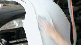 Ο μηχανικός προετοιμάζει το σώμα αυτοκινήτων του αυτοκινήτου για τη ζωγραφική Λείανση του σώματος αυτοκινήτων απόθεμα βίντεο