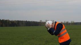 Ο μηχανικός σε ένα προστατευτικές κράνος και μια φανέλλα παίρνει το καταφύγιο από το σήμα αέρα απόθεμα βίντεο