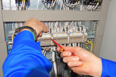 Ο μηχανικός στερεώνει τα ηλεκτρικά καλώδια στα τερματικά του ηλεκτρικού γραφείου με το κατσαβίδι Στοκ εικόνα με δικαίωμα ελεύθερης χρήσης