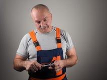Ο μηχανικός στην κατασκευή ασθμαίνει το κράτημα trammel Στοκ Εικόνες