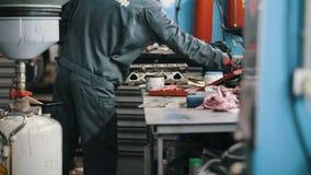 Ο μηχανικός στην υπηρεσία αυτοκινήτων που καθορίζει και που επισκευάζει τη λεπτομέρεια του αυτοκινήτου, το υπόβαθρο απόθεμα βίντεο
