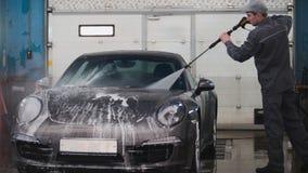 Ο μηχανικός στην υπηρεσία αυτοκινήτων πλένει sportcar suds από τις μάνικες νερού Στοκ Εικόνες